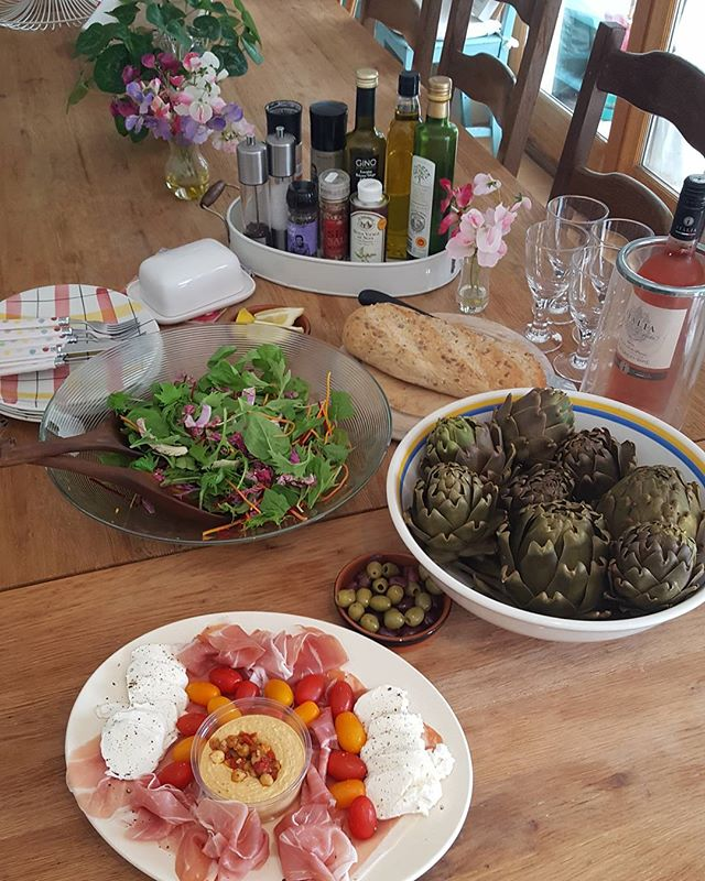 Homegrown and healthy Summer lunch in the UK sun.  Lunch Italian-style by the pool. Home grown artichokes, Isle of Wight tomatoes, humous,  salad with rocket, spinach, grated carrot and beetroot, mozzarella cheese, parma ham, olives and rose PInot Grigio wine and fresh bread. Delicious!